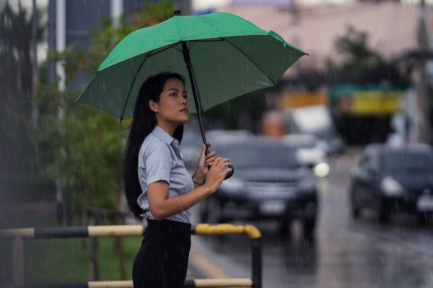 Azjatka Używa Parasola Podczas Deszczu. Idzie Przez Ulicę Darmowe Zdjęcia