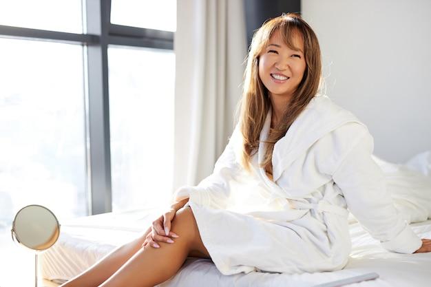 Azjatka W Szlafroku Siedzi Uśmiechnięta, Na łóżku W Jasnej Sypialni, Cieszyć Się Samotnymi Wakacjami Premium Zdjęcia