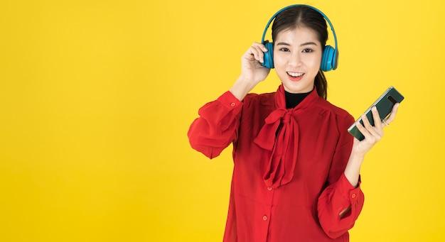 Azjatki W Radosnym Nastroju Trzymają Telefon I Zakładają Bezprzewodowe Słuchawki Z Czerwoną Sukienką. Premium Zdjęcia