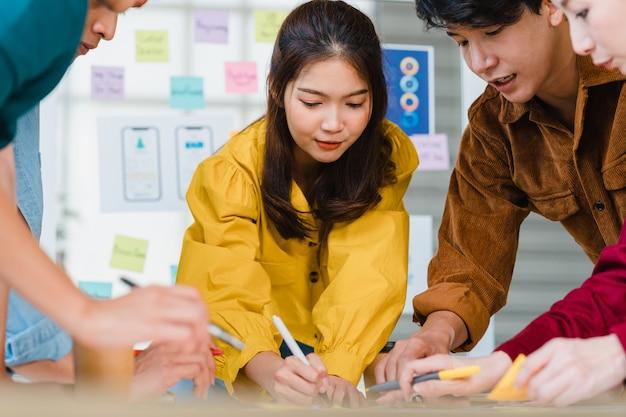 Azjatyccy Biznesmeni I Biznesmeni Spotykają Się Podczas Burzy Mózgów Na Temat Kreatywnej Aplikacji Do Planowania Projektowania Stron Internetowych I Opracowywania Układu Szablonu Dla Projektu Telefonu Komórkowego Współpracującego W Małym Biurze. Darmowe Zdjęcia