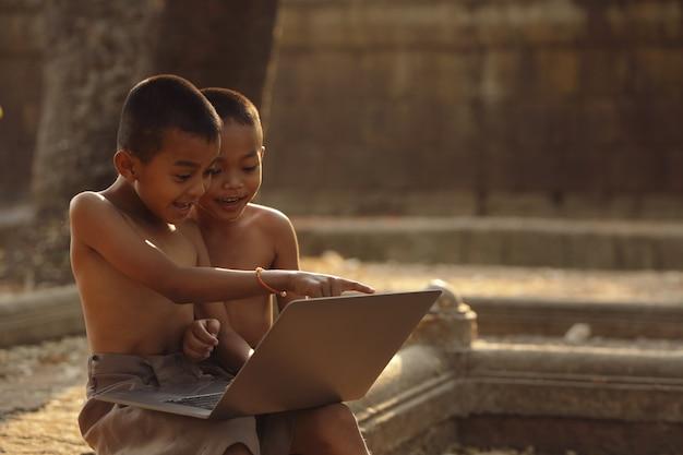 Azjatyccy Chłopcy świetnie Się Bawią, Szukając Informacji W Internecie. Premium Zdjęcia