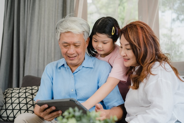 Azjatyccy dziadkowie i wnuczka używa pastylkę w domu. starszy chińczyk, dziadunio i babcia szczęśliwi, wydajemy rodzinnemu czasowi relaksować z młodą dziewczyną sprawdza ogólnospołecznych środki, kłama na kanapie w żywym izbowym pojęciu Darmowe Zdjęcia