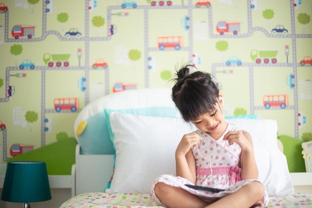 Azjatyccy Dzieci Używa Hełmofon Dla Słuchają Muzykę Smartphone Na łóżku W Jej Dekorującej Sypialni Premium Zdjęcia