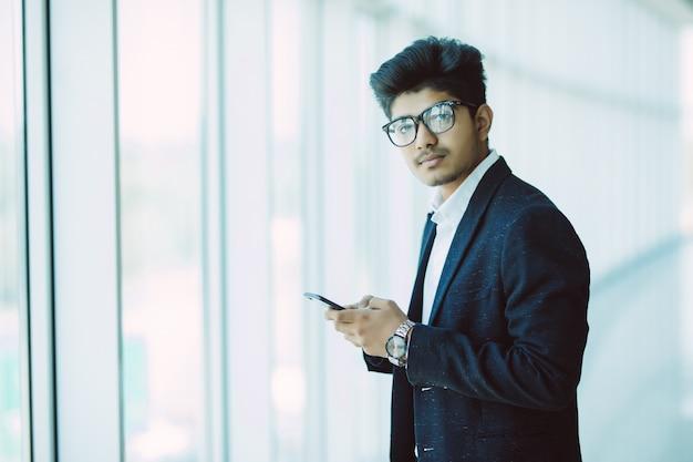 Azjatyccy Indiańscy Ludzie Biznesu Texting Używać Smartphone Podczas Gdy Chodzący W Nowożytnym Biurze Darmowe Zdjęcia