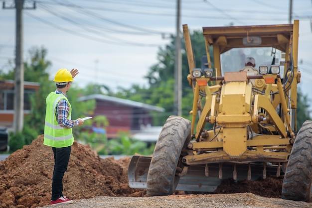 Azjatyccy Inżynierowie Obserwują Przebudowę Drogi I Kontrolują Budowę Drogi Na Placu Budowy. Premium Zdjęcia