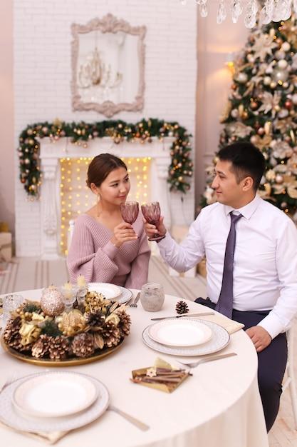 Azjatyccy Mężczyźni I Kobiety świętują Boże Narodzenie, Pijąc Wino Przy Stole Jadalnym Przy Drzewie I Kominku Premium Zdjęcia