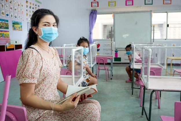 Azjatyccy Nauczyciele I Uczniowie Noszą Maski W Klasie I Szkole, Która Ma Się Rozpocząć Premium Zdjęcia