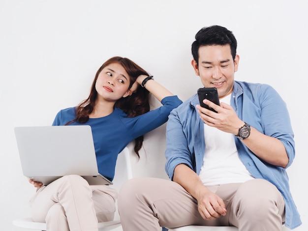 Azjatyccy Potomstwa Dobierają Się Kochanka Walczy Dla Mądrze Telefonu W żywym Pokoju W Domu. Premium Zdjęcia