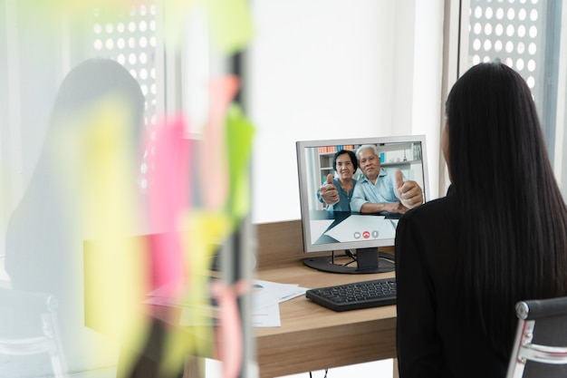 Azjatyccy Rodzice Biorą Udział W Wideokonferencji Z Córką Podczas Wakacji. Premium Zdjęcia