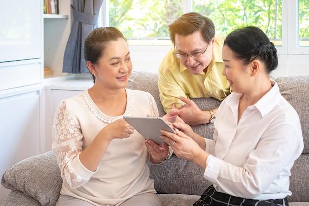 Azjatyccy starsi ludzie, dziadkowie używa cyfrową pastylkę w domu, szczęśliwa rodzina używa technologii pojęcie Premium Zdjęcia