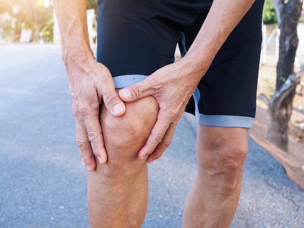 Azjatyccy Starsi Mężczyźni Z Bólem Kolana I Bólem Mięśni Spowodowanym ćwiczeniami Z Bieganiem. Premium Zdjęcia