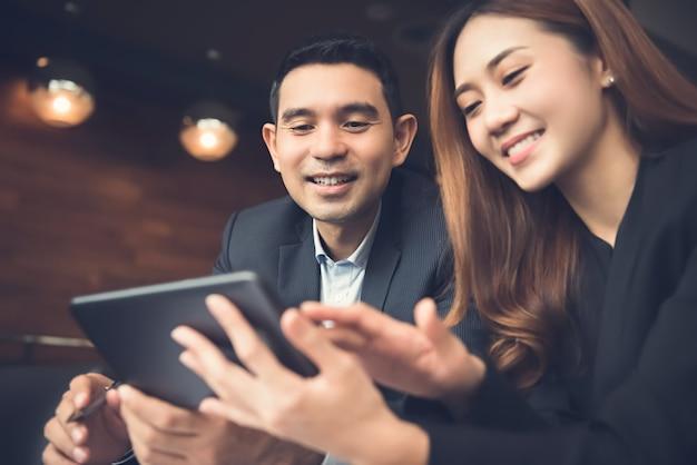 Azjatycka biznesowa para cieszy się używać pastylka komputerowego surfuje internet w kawiarni Premium Zdjęcia