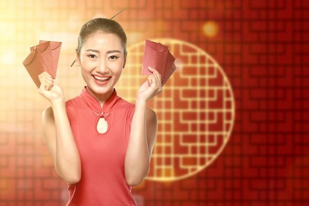 Azjatycka Chinka W Cheongsam Sukni Trzyma Czerwone Koperty Premium Zdjęcia