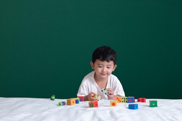 Azjatycka Chłopiec Sztuki Zabawka Lub Kwadratowego Bloku łamigłówka Na Zielonym Chalkboard Premium Zdjęcia
