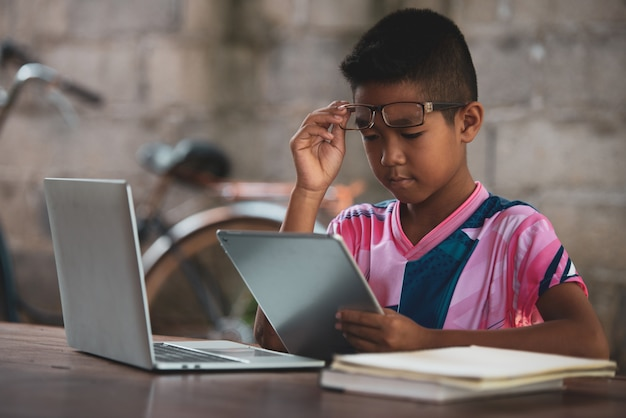 Azjatycka chłopiec używa laptop na stole, wraca czerpać Darmowe Zdjęcia