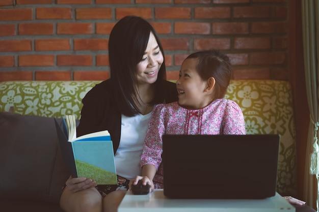 Azjatycka Córka I Matka Używa Komputerowego Laptop W Domu Z Uśmiechem I Szczęśliwy. Premium Zdjęcia