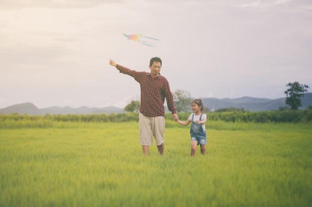 Azjatycka Dziecko Dziewczyna, Ojciec Z Kanią Bieg I Szczęśliwy Na łące W Lecie W Naturze Premium Zdjęcia