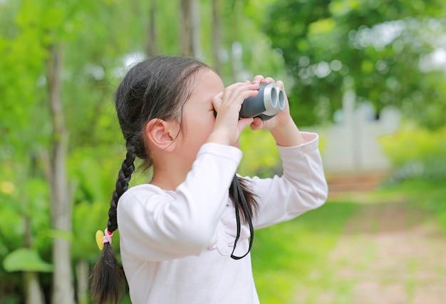 Azjatycka dziecko dziewczyna z lornetkami w natur polach Premium Zdjęcia