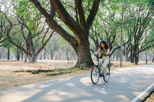 Azjatycka Dziewczyna Jedzie Bicykl Na Drodze W Parku Z Uśmiech Twarzą Premium Zdjęcia