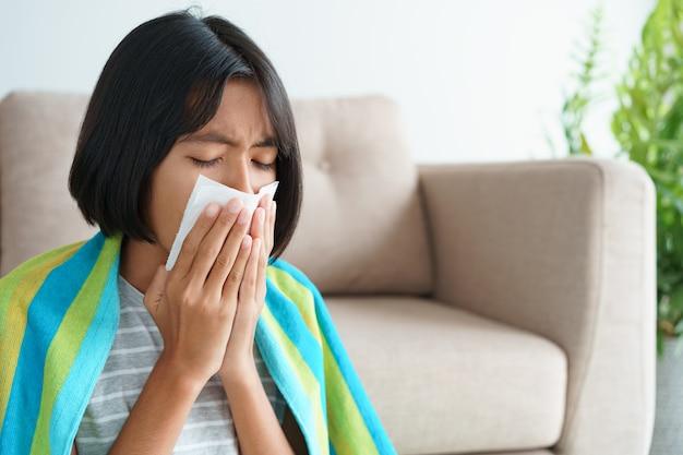 Azjatycka Dziewczyna Ma Sezon Grypowy I Kicha Przy Użyciu Papierowych Chusteczek, Siedząc W Salonie W Domu. Premium Zdjęcia
