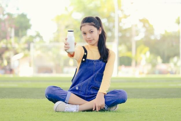 Azjatycka Dziewczyna Pije Pyszną Butelkę Mleka. Premium Zdjęcia