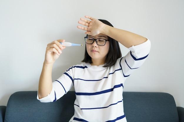 Azjatycka Dziewczyna Trzyma Termometr Sprawdź Temperaturę Ciała Samodzielnie. Pojęcie Opieki Medycznej Premium Zdjęcia