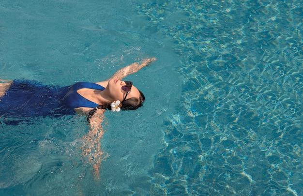 Azjatycka dziewczyna z pływackim apartamentem i słońc szkłami na basenie Premium Zdjęcia