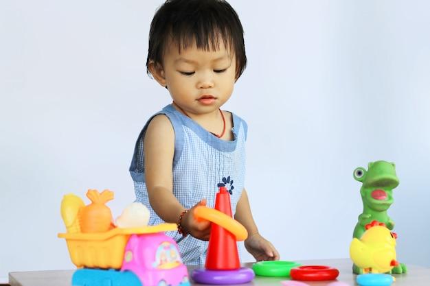 Azjatycka Dziewczynka Bawić Się Z Wiele Zabawkami. Premium Zdjęcia