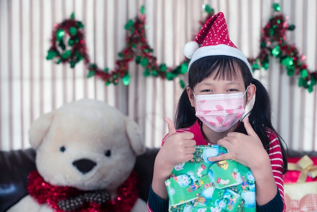 Azjatycka Dziewczynka Trzyma Pudełko Z Maską Nosić W Boże Narodzenie Premium Zdjęcia