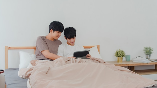 Azjatycka Homoseksualna Para Używa Pastylkę W Domu. Młodzi Azjaci Lgbtq + Mężczyźni Z Radością Odpoczywają Razem Po Przebudzeniu, Sprawdzają Pocztę I Media Społecznościowe Rano Na łóżku W Sypialni W Domu. Darmowe Zdjęcia
