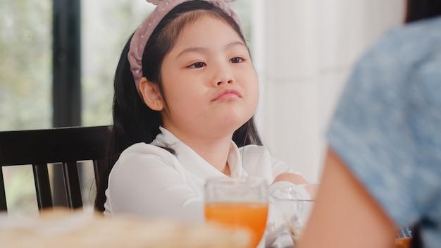 Azjatycka japońska córka znudzona jedzeniem. dzieci w stylu życia smutne nie lubią jedzenia zdenerwowanego śniadania w nowoczesnej kuchni w domu rano. Darmowe Zdjęcia