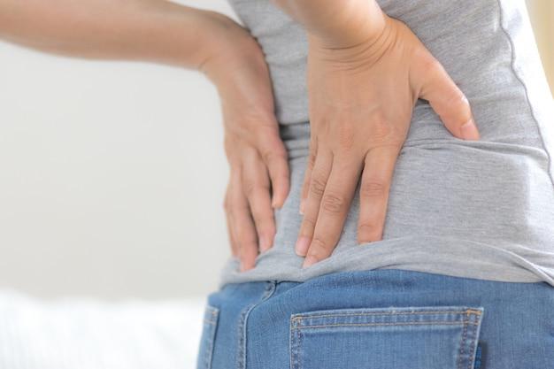 Azjatycka kobieta czuje ból na plecach i biodrze, źle się czuje w salonie. pojęcie opieki zdrowotnej i medycznej. Premium Zdjęcia