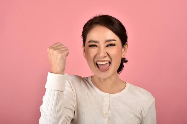 Azjatycka Kobieta Czuje Się Szczęśliwa I Podekscytowana Na Osiągnięciu Sukcesu Na Różowej ścianie Premium Zdjęcia