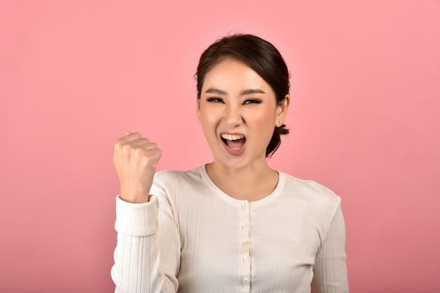 Azjatycka Kobieta Czuje Się Szczęśliwa I Podekscytowana Na Osiągnięciu Sukcesu Na Różowym Tle, Portret Uśmiechnięta Zwycięzca Dziewczyna świętuje Use Dla Reklamy. Premium Zdjęcia