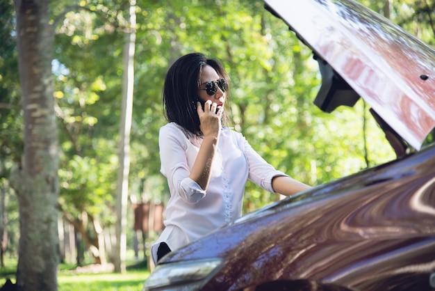 Azjatycka kobieta dzwoni mechanika lub ubezpieczenia personel naprawiać problem z silnikiem samochodowym na lokalnej drodze Darmowe Zdjęcia