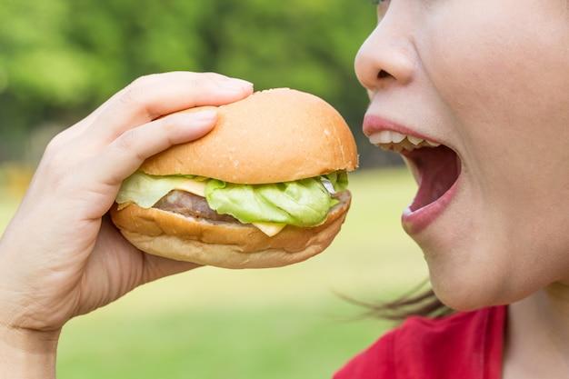 Azjatycka Kobieta Je Hamburger Bardzo Głodnego. Premium Zdjęcia