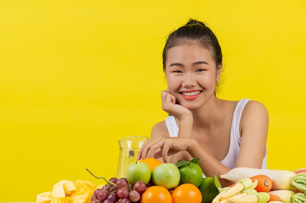 Azjatycka Kobieta Jest Ubranym Białego Podkoszulek Bez Rękawów. Stół Jest Pełen Wielu Rodzajów Owoców. Darmowe Zdjęcia