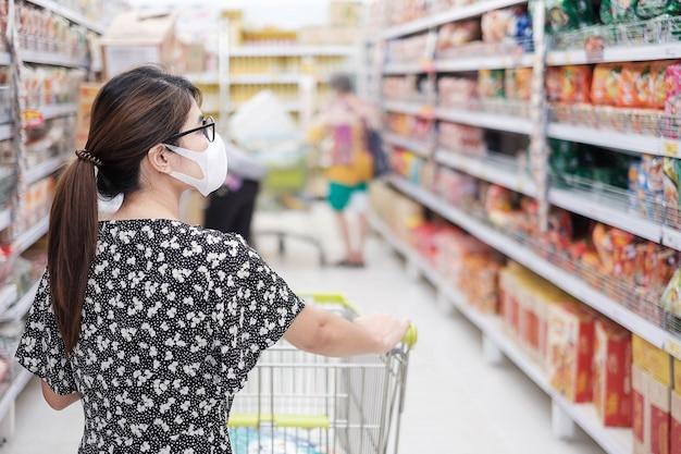 Azjatycka Kobieta Jest Ubranym Maskę Ochronną I Robi Zakupy W Supermarkecie Lub Sklepie Spożywczym, Ochrania Coronavirus Inflection. Dystans Społeczny, Nowa Normalność I życie Po Pandemii Covida-19 Premium Zdjęcia