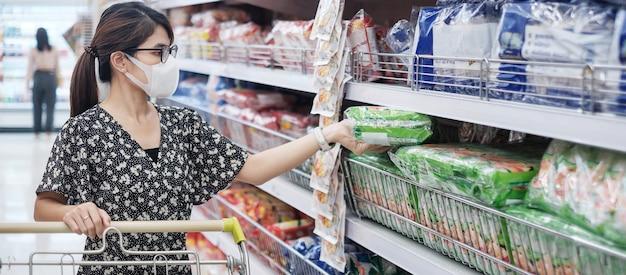 Azjatycka Kobieta Jest Ubranym Ochronną Maskę I Trzyma Produkty żywnościowe Podczas Robić Zakupy W Supermarkecie Lub Sklepie Spożywczym, Ochrania Coronavirus Inflection. Dystans Społeczny, Nowa Normalność I życie Po Pandemii Covida-19 Premium Zdjęcia