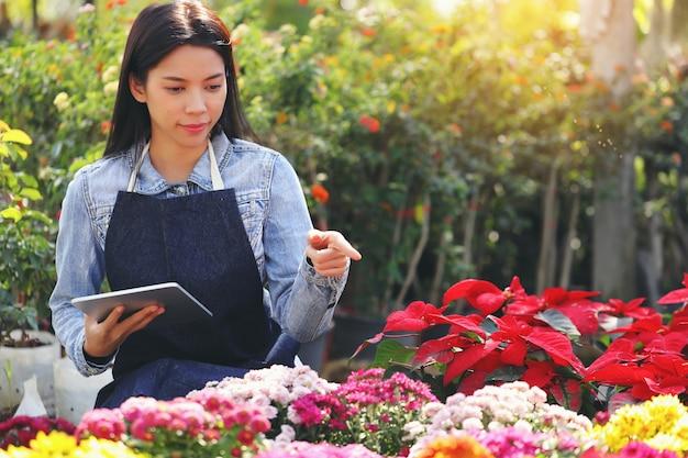 Azjatycka Kobieta, Która Jest Właścicielem Firmy Zajmującej Się Ogrodem Kwiatowym, Liczy Kwiaty Zgodnie Z Zamówieniem Klienta. Premium Zdjęcia
