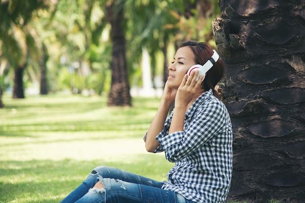 Azjatycka Kobieta Lubi Słuchać Muzyki Online Pod Drzewem W Publicznym Parku. Relaks Technologia Internet Koncepcji Tings Premium Zdjęcia