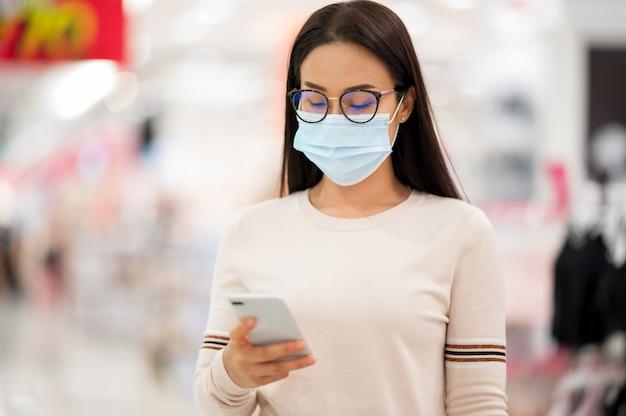 Azjatycka Kobieta Ma Na Sobie Maskę I Trzyma Telefon Komórkowy Na Zakupy W Domu Towarowym Podczas Wirusa Koronowego Premium Zdjęcia