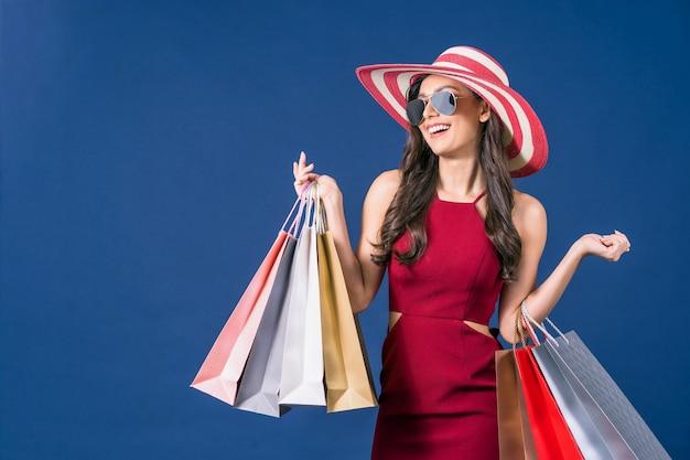 Azjatycka Kobieta Nosi Okulary Przeciwsłoneczne I Noszenie Kolorowych Toreb Na Zakupy Na Niebieskim Tle Premium Zdjęcia