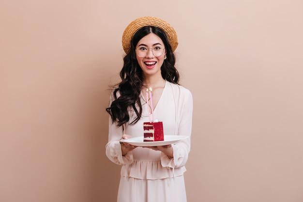 Azjatycka Kobieta Patrząc Na Kamery Z Uśmiechem. Szczęśliwa Japonka Trzyma Tort W Słomkowym Kapeluszu. Darmowe Zdjęcia