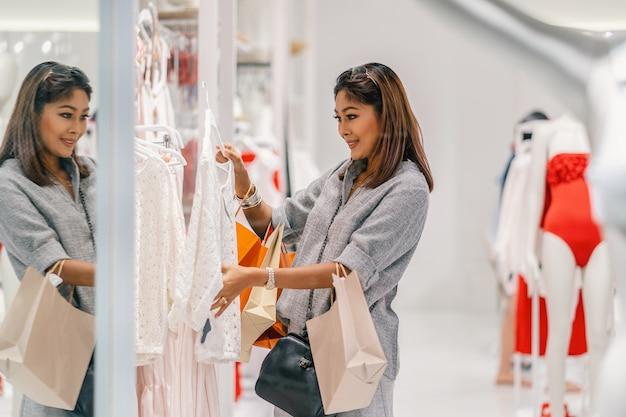 Azjatycka kobieta patrzeje bieliznę w sklepie i wybiera z szczęśliwą akcją przy wydziałowym centrum wybiera Premium Zdjęcia