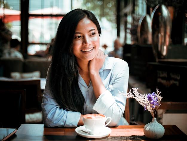 Azjatycka kobieta pije kawę i działanie z laptopem w kawiarni Premium Zdjęcia