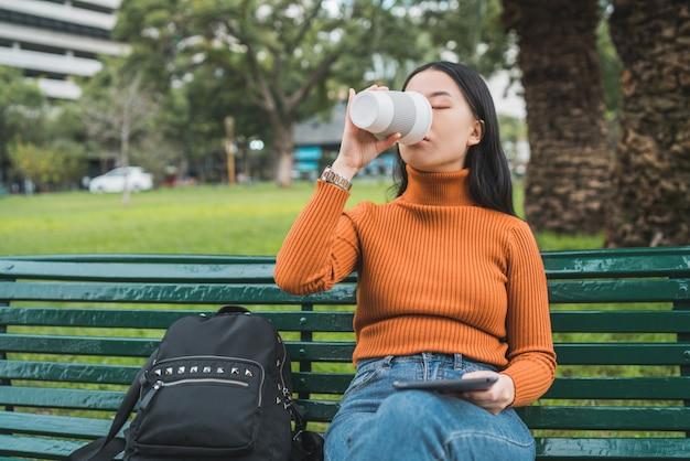 Azjatycka Kobieta Pije Kawę I Używa Pastylkę. Darmowe Zdjęcia