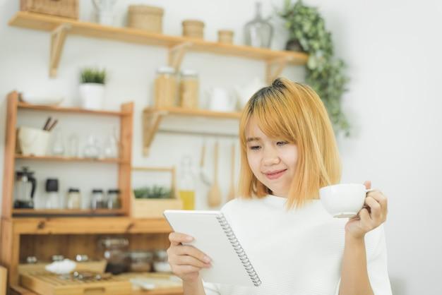 Azjatycka Kobieta Pisze Listach Zakupów W Notepad Piórem Na Jej Kuchennym Kontuarze I Czytaniu W Domu Darmowe Zdjęcia