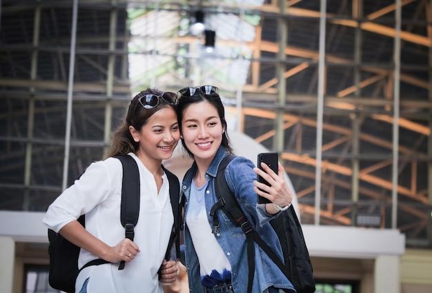 Azjatycka kobieta podróżuje z telefonem komórkowym Premium Zdjęcia