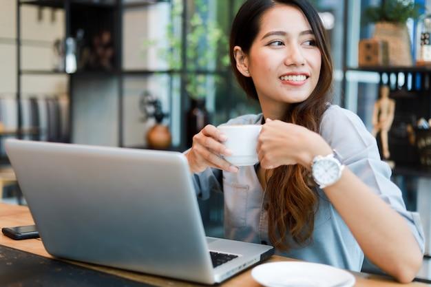 Azjatycka kobieta pracuje kawę w kawiarni i pije z laptopu uśmiechem i szczęśliwą pracą Premium Zdjęcia